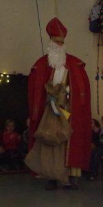 Der Nikolaus steht in der Turnhalle der Kindergarteninitiative Ü-Dötzchen in Bonn und hält einen großen Sack und den Händen